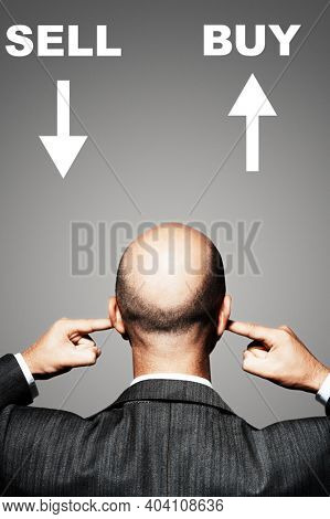 Angry investor not knowing whether to buy or sell his shares so he is putting his fingers in his ears whilst looking at a sign saying sell down and buy up