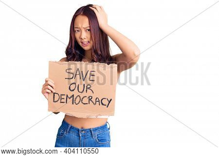 Young beautiful chinese girl holding save our democracy protest banner stressed and frustrated with hand on head, surprised and angry face