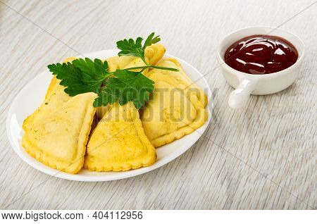 Small Savory Pies, Leaves Of Parsley In Glass White Saucer, Sauce Boat With Ketchup On Wooden Table