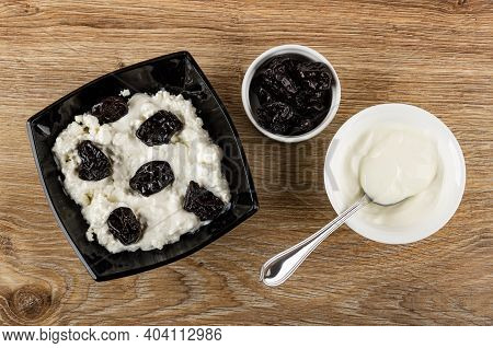Cottage Cheese With Sour Cream And Prunes In Black Glass Bowl, Bowl With Prune, Spoon In White Bowl