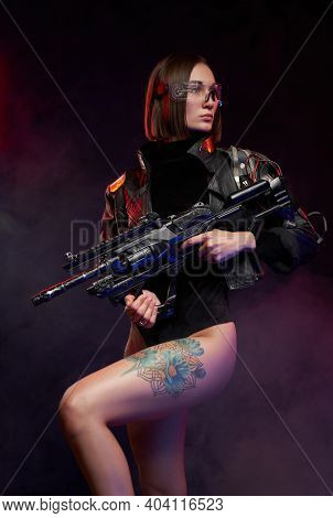 Sexual Female Warrior With Nude And Tattooed Legs Poses In Dark And Smokey Background. Armed With Fu