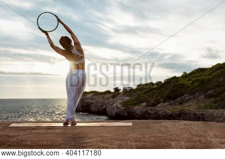 Young Woman Exercise Yoga In Nature Sky & Sea View. Easy Yoga Poses For Beginners With Yoga Wheel In