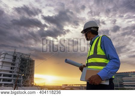 Engineering Consulting People On Construction Site Holding Blueprint And Laptop, Daily Book In His H