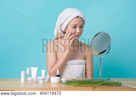 Beautiful Asian Young Woman Smiling While Touching Face And Looking At The Mirror With Cosmetics Moc