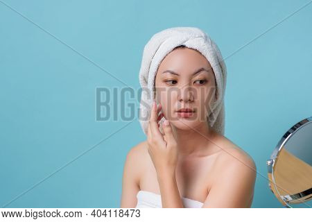 Beautiful Asian Young Woman Touching Face While Looking At The Mirror. Skincare And Clean Concept, B