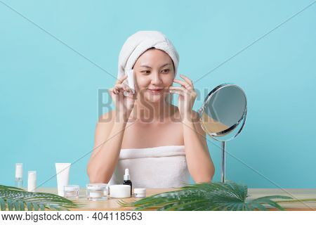 Beautiful Asian Young Woman Smiling And Holding A Mockup Cream Product While Looking At Mirror And T