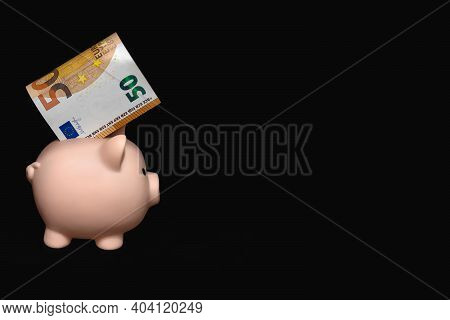 A Piggy Bank With A 50 Euro Bill Inside On A Black Background. The Concept Of Saving Money. Careful