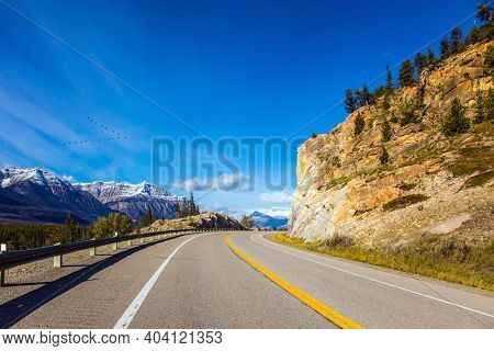 Magnificent Indian summer in the Canadian Rockies. The sharp peaks of the Rocky Mountains are clearly visible against the blue sky. Asphalt highway leads to Abraham Lake