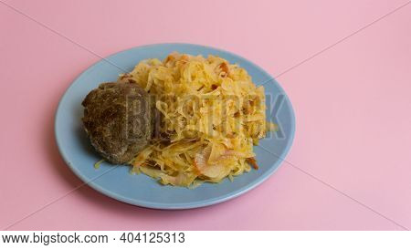 Stewed White Cabbage With A Cutlet Steak On A Plate. A Dish Of Russian, Polish Cuisine. Garnish In T