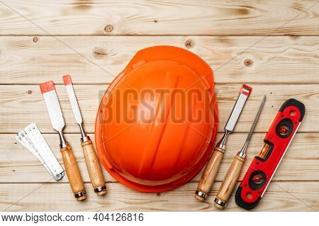Construction Worker Tools Hardhat And Chisel On Wooden Background