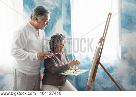 Asian Elderly Couple Painting On Canvas At Their Home. Happy Smiling Old Man And Woman Colouring Tog