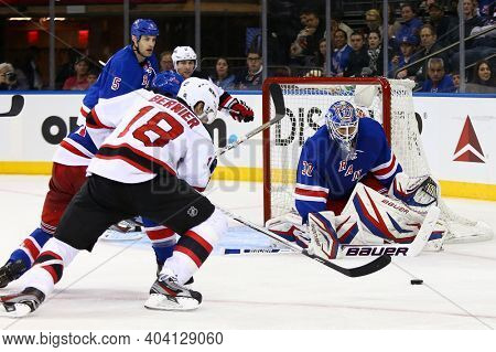NEW YORK-APR 27: New Jersey Devils right wing Steve Bernier (18) chases the puck near New York Rangers goalie Henrik Lundqvist (30) at Madison Square Garden on April 27, 2013 in New York City.