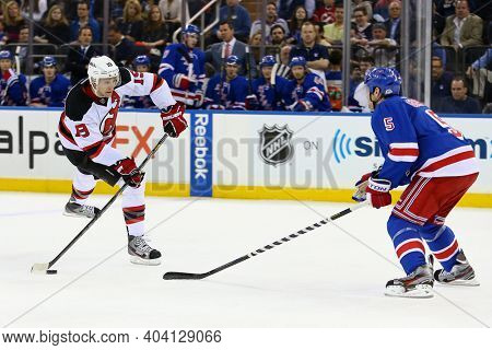 NEW YORK-APR 27: New Jersey Devils center Travis Zajac (19) looks to pass the puck beyond New York Rangers defenseman Dan Girardi (5) at Madison Square Garden on April 27, 2013 in New York City.