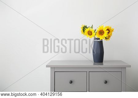 Bouquet Of Beautiful Sunflowers In Vase On Commode Near Light Wall. Space For Text