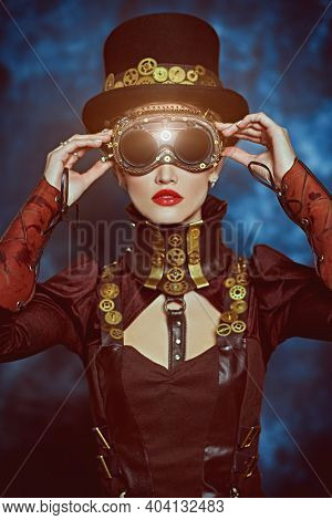 Portrait of a beautiful victorian steampunk lady on a grunge background. Fantasy world, scientific inventions.