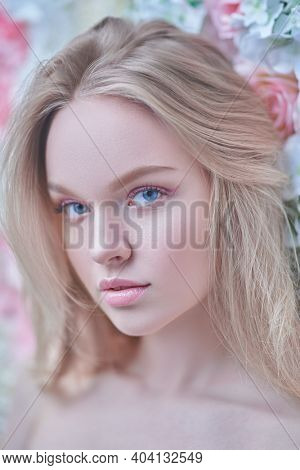 Spring girl. Portrait of a beautiful young woman with light makeup in pink colors and blonde hair on a background of blooming roses. Beauty concept.