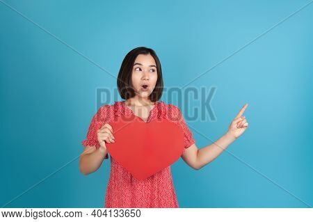 Close-up A Surprised, Shocked, Startled Young Asian Woman With Her Mouth Open In A Red Dress Holds A