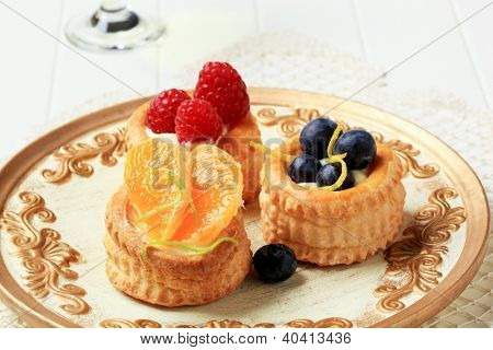 puff pastry cakes decorated with fresh fruit, on the plate
