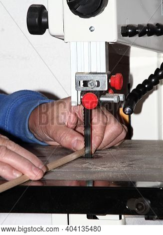 Man With An Electrical Jig Saw In An Action At The Workshop. Focused On The Blade With Saw Teeth Dur
