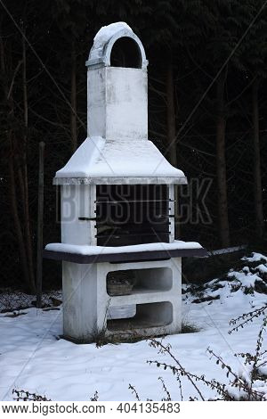 Fireplace In The Garden At Winter Time. Fireplace Near The Fence  Is Covered With Snow.