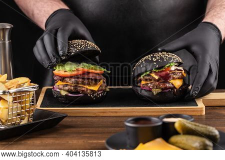 Making burger. Chef hands in black gloves are closing top black bun of burger with double beef cutlet, cheese and vegetables.
