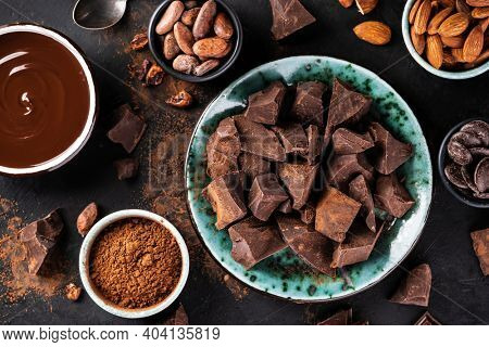 Broken pieces of chocolate in a vintage bowl and ingredients for making chocolate sweets on a dark textured background, top view. Confectionery chocolate background. Chunks of chocolate.