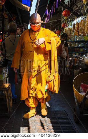 Chinatown, Bangkok, Thailand - Nov. 14, 2020: A Chinese Monk, With A Protective Facemask And A Bottl