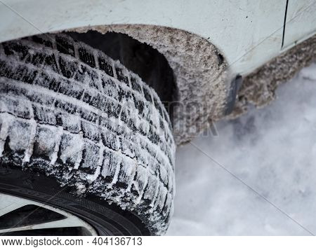 Selective Focus. Close-up Of A Winter Car Tire Tread With Snow And Ice. The Use Of Special Tires In