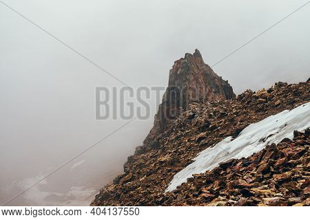 Beautiful Pointy Cliff On High Rocky Mountain Edge With Snow Among Thick Low Clouds. Atmospheric Min