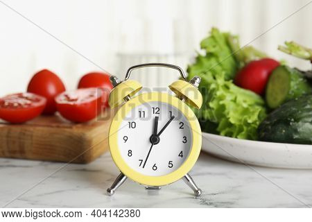 Alarm Clock And Vegetables On White Marble Table. Meal Timing Concept