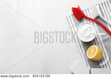 Flat Lay Composition With Baking Soda And Brushes On White Table. Space For Text