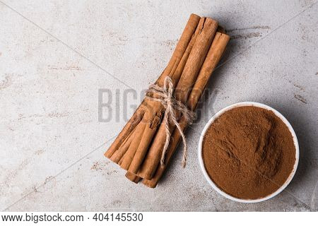 Aromatic Cinnamon Sticks And Powder On Light Table, Flat Lay. Space For Text