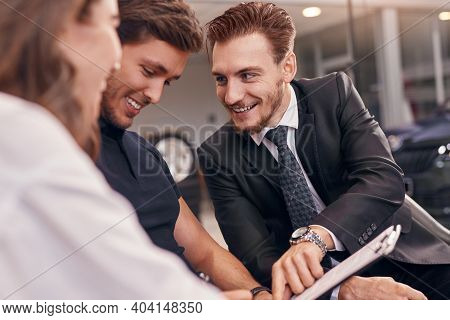 Happy Man In Suit Smiling And Demonstrating Insurance Contract To Couple While Working In Car Dealer
