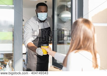 An African Waiter Wearing Mask And Gloves Giving A Paper Cup Of Hot Coffee To A Female Customer Thro