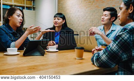 Group Of Happy Young Asia Business Coworkers Using Laptop In Team Casual Meeting, Startup Project Di