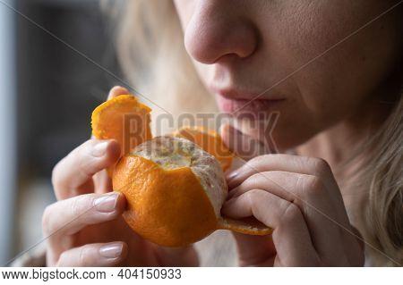 Sick Woman Trying To Sense Smell Of Fresh Tangerine Orange, Has Symptoms Of Covid-19, Corona Virus I