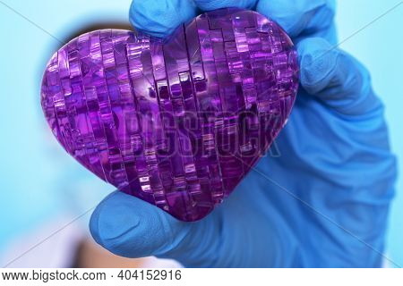 A Hand In A Medical Glove Holds The Heart. The Concept Of Medicine And Rehabilitation.