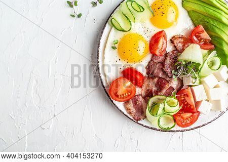 Healthy Nutritious Paleo Keto Breakfast. Fried Eggs, Bacon, Avocado, Cheese And Fresh Salad. On Whit