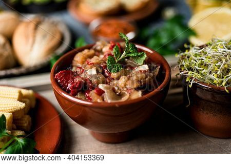 a bowl with some escalivada, a side dish made with eggplant, onion and red pepper typical of catalonia, spain, and some sprouted kale seeds in a bowl, on a table with some other vegan ingredients