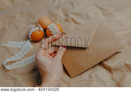 Decorating Easter Eggs On Kraft Paper With Lace And Rope. Three Easter Eggs On Crumpled Kraft Paper
