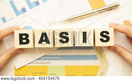 Cropped View Of Hands Holding Wooden Cubes With Basis Lettering On Work Table. Top View