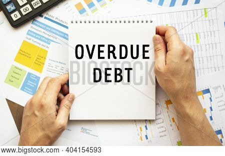 Businessman Hold Notepad With Text Overdue Debt. Financial Charts On The Desktop. Financial And Busi