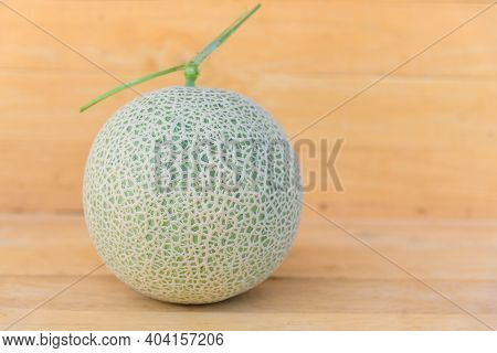 Focus To Fresh Green Melon On Wood Plate