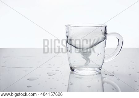 Transparent Glass Mug With Water On Light Surface With Water Drops. Water In The Form Of Tornado Ins