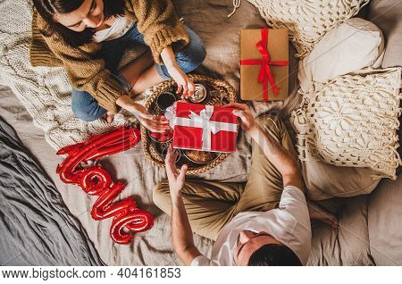 Young Happy Couple Sitting On Blankets In Bed At Home And Giving Presents In Boxes Over Breakfast An