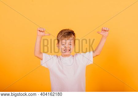 Portrait Of Happy Little Boy Over Yellow Background