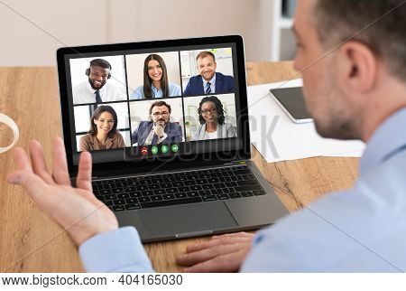 Businessman Having Virtual Corporate Meeting Via Video Call On Laptop Communicating With Employees O