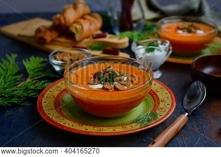 Close-up Of Orange Puree Soup With Baked Peppers And Tomatoes On Beautiful Plates With Croutons And