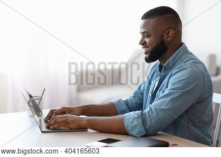Smiling Millennial African American Man Working With Laptop At Home Office. Handsome Black Self-empl