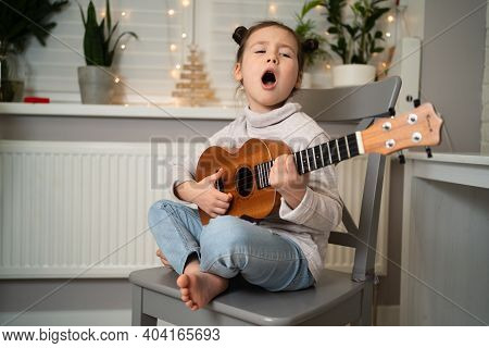 Plays The Ukulele And Sings. Early Childhood Development. The Girl Has Musical Talent. Beautiful Lit